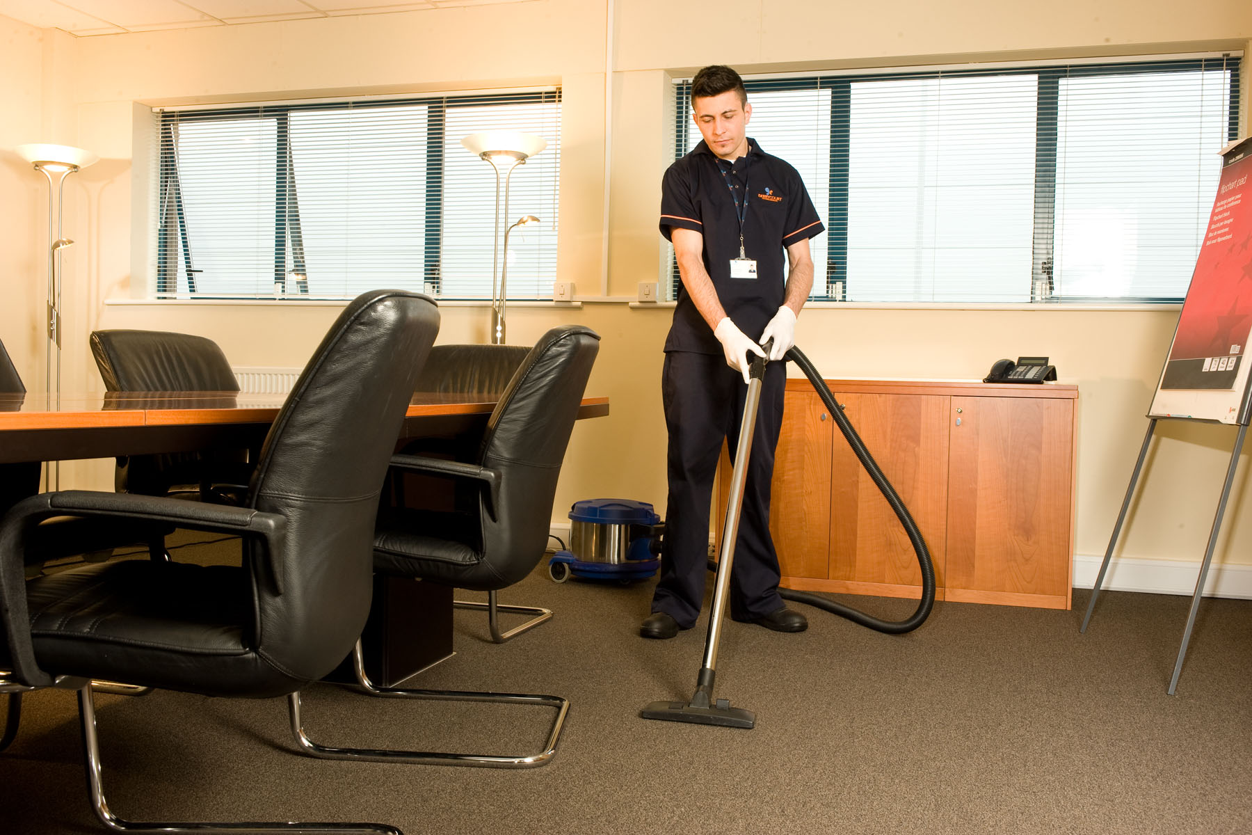 A Staff Member Vacuum Cleaning in the Office